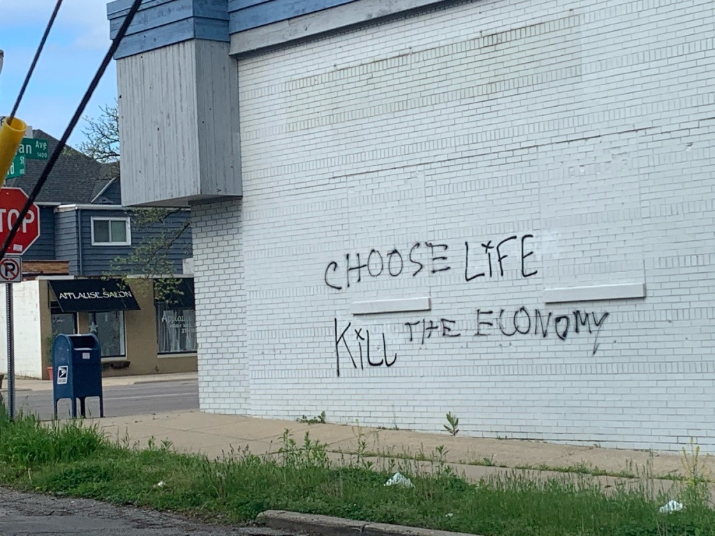 "graffiti of the words ""choose life / kill the economy"" on the side of a painted brick building"